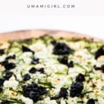 pesto and feta pizza with zucchini and black olives on a pizza peel