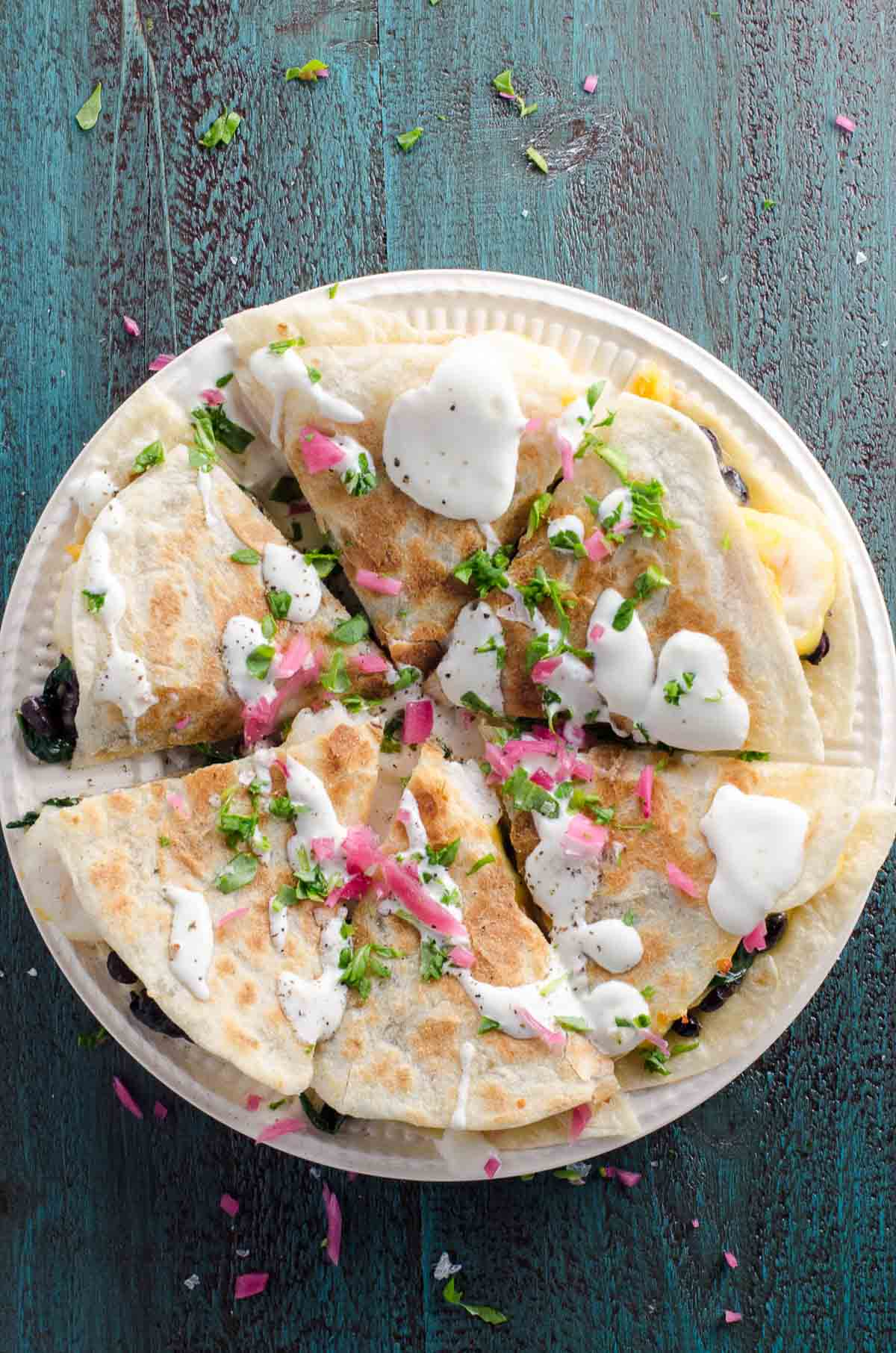 a shrimp quesadilla with spinach topped with sour cream, pickled onions, and scallions on a blue background