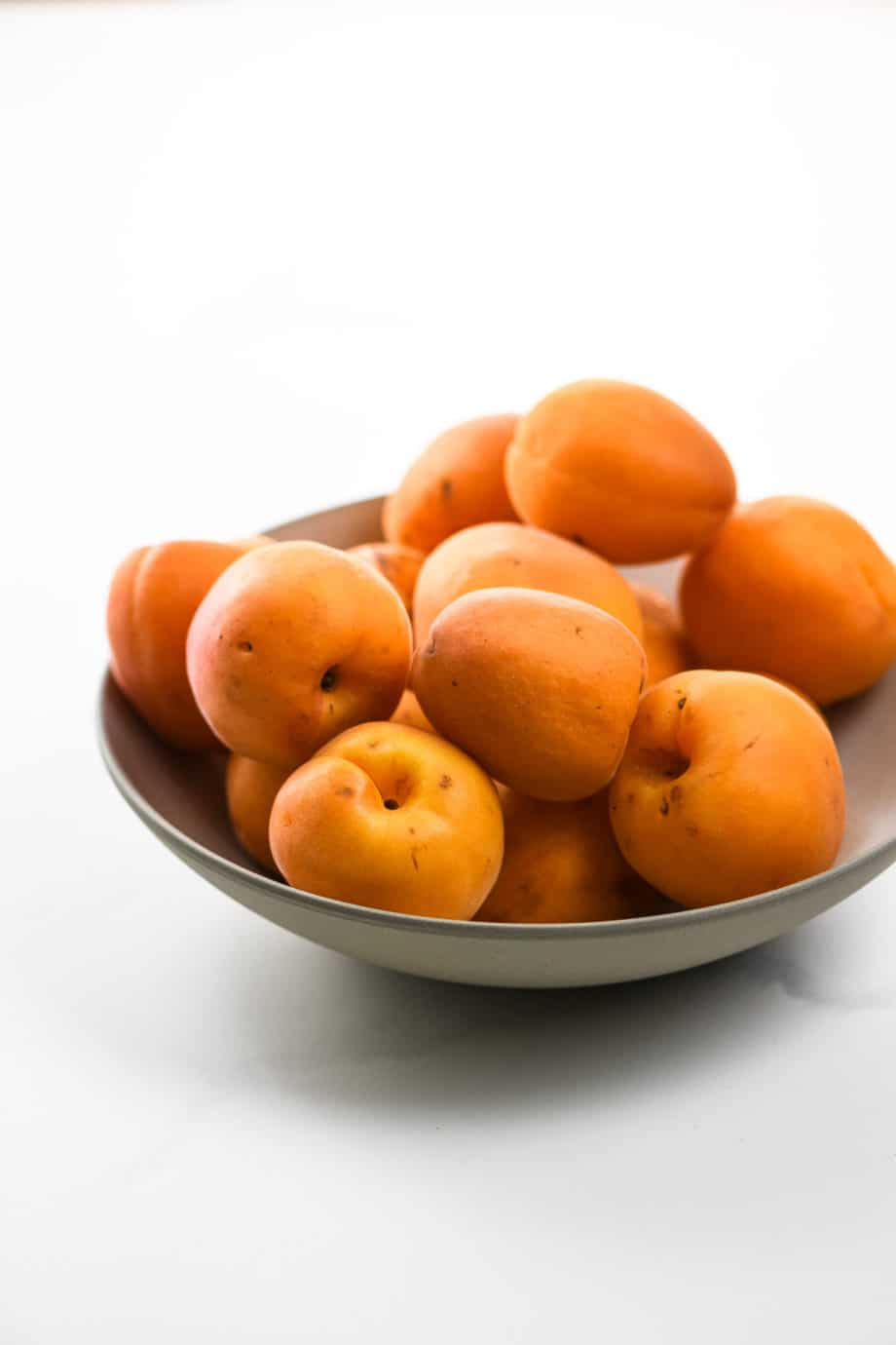 fresh apricots in a taupe colored bowl