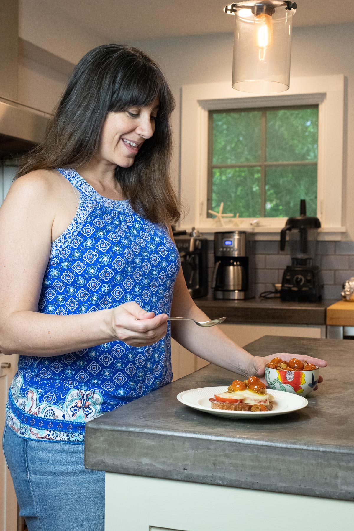 Carolyn Gratzer Cope spooning tomato confit over an open face grilled cheese
