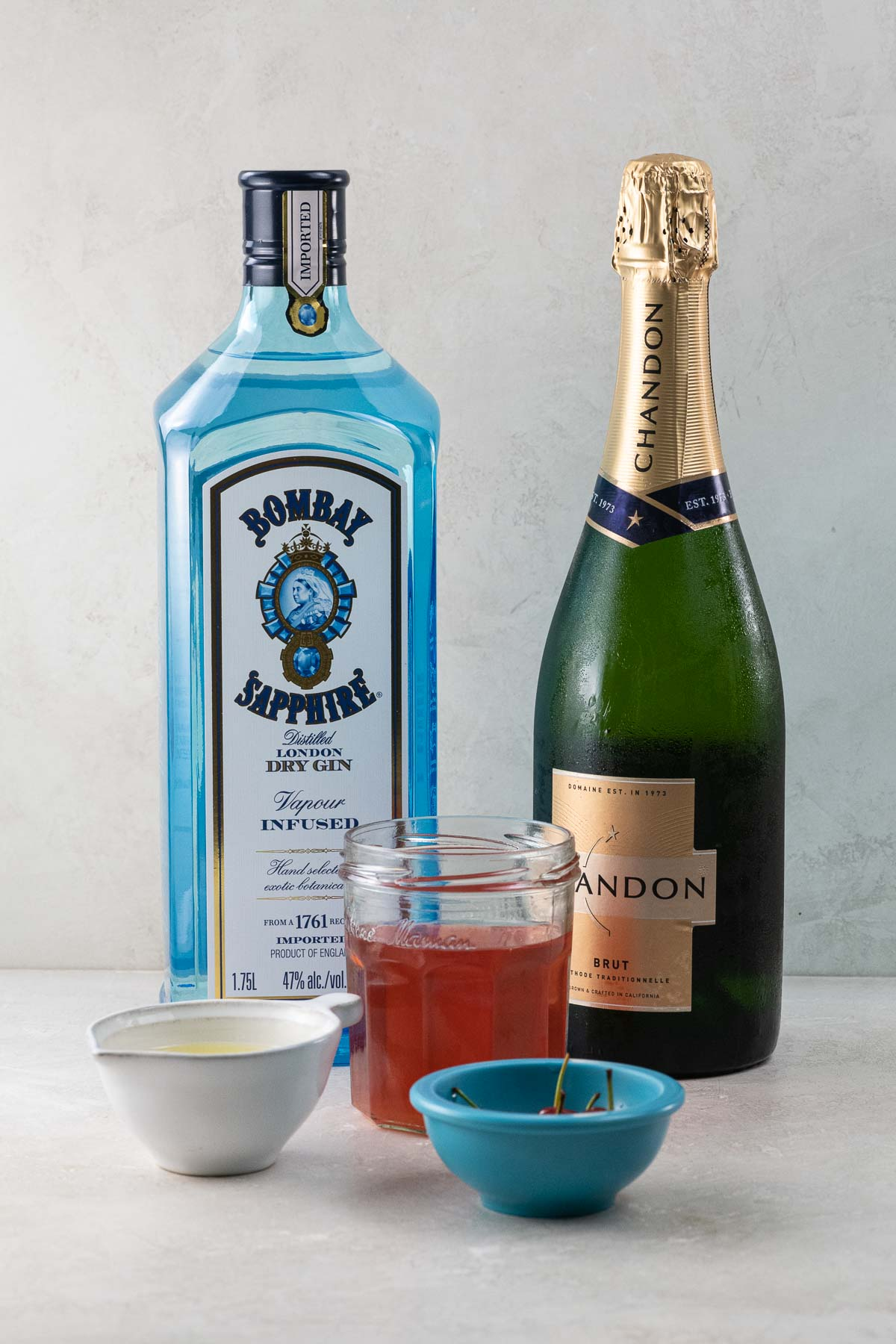 a bottle of sapphire gin, a bottle of chandon sparkling wine, sour cherry syrup, lemon juice, and cherries