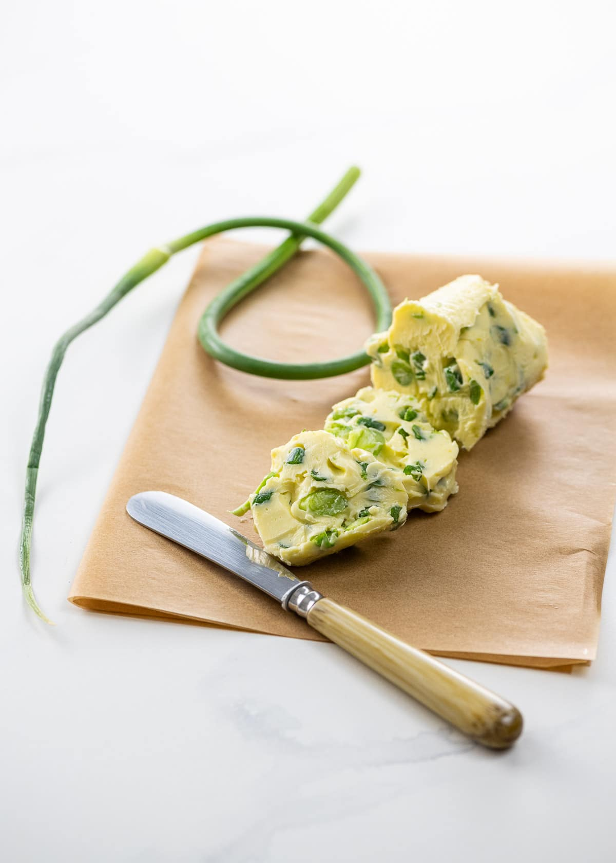 garlic scape butter on parchment with a small knife and a garlic scape