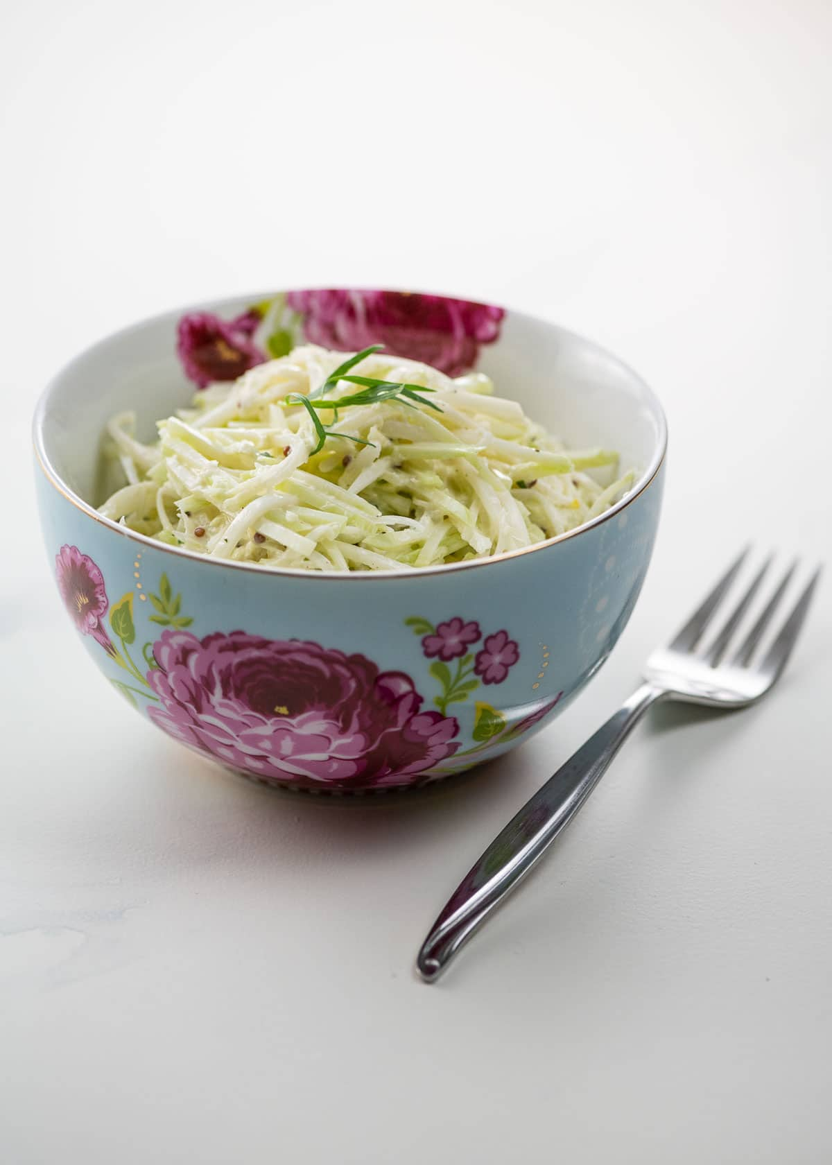 kohlrabi remoulade in a beautiful blue and pink bowl with a fork