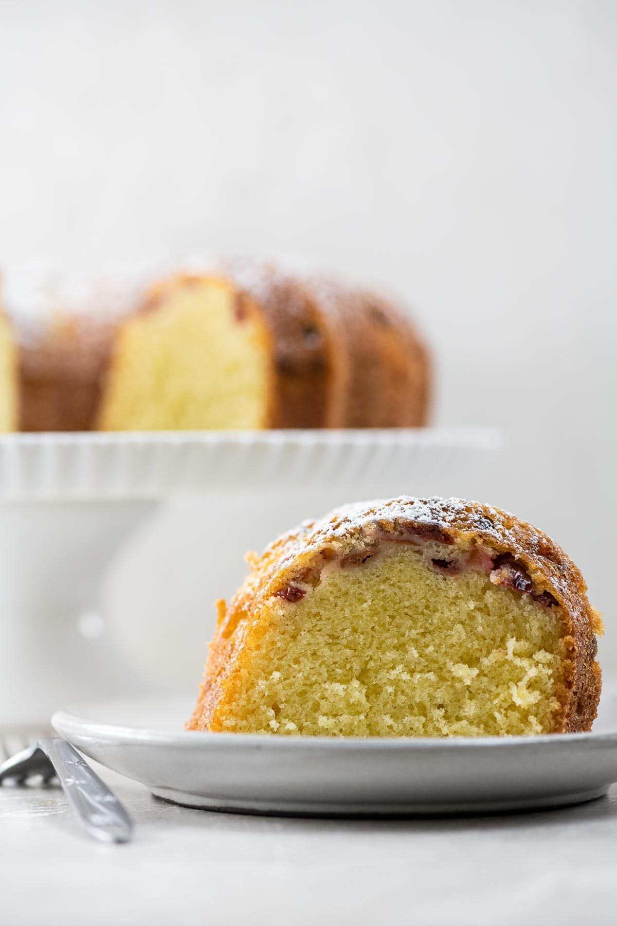 a slice of sour cherry cake on a plate with the rest of the cake on a stand behind it