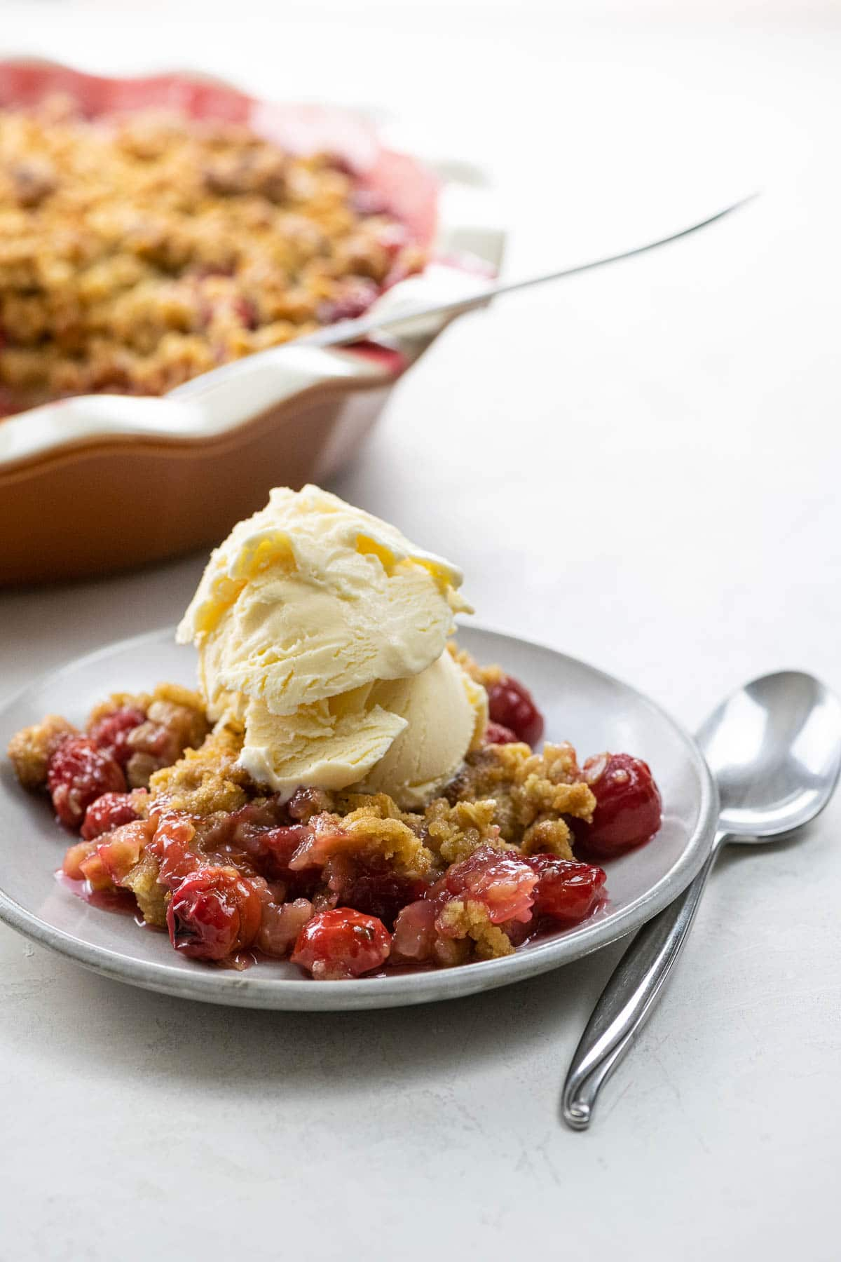 sour cherry crisp a la mode in a deep dish pie plate and on a plate