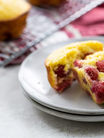 a sour cherry muffin on plates with more on a cooling rack and red and white towel