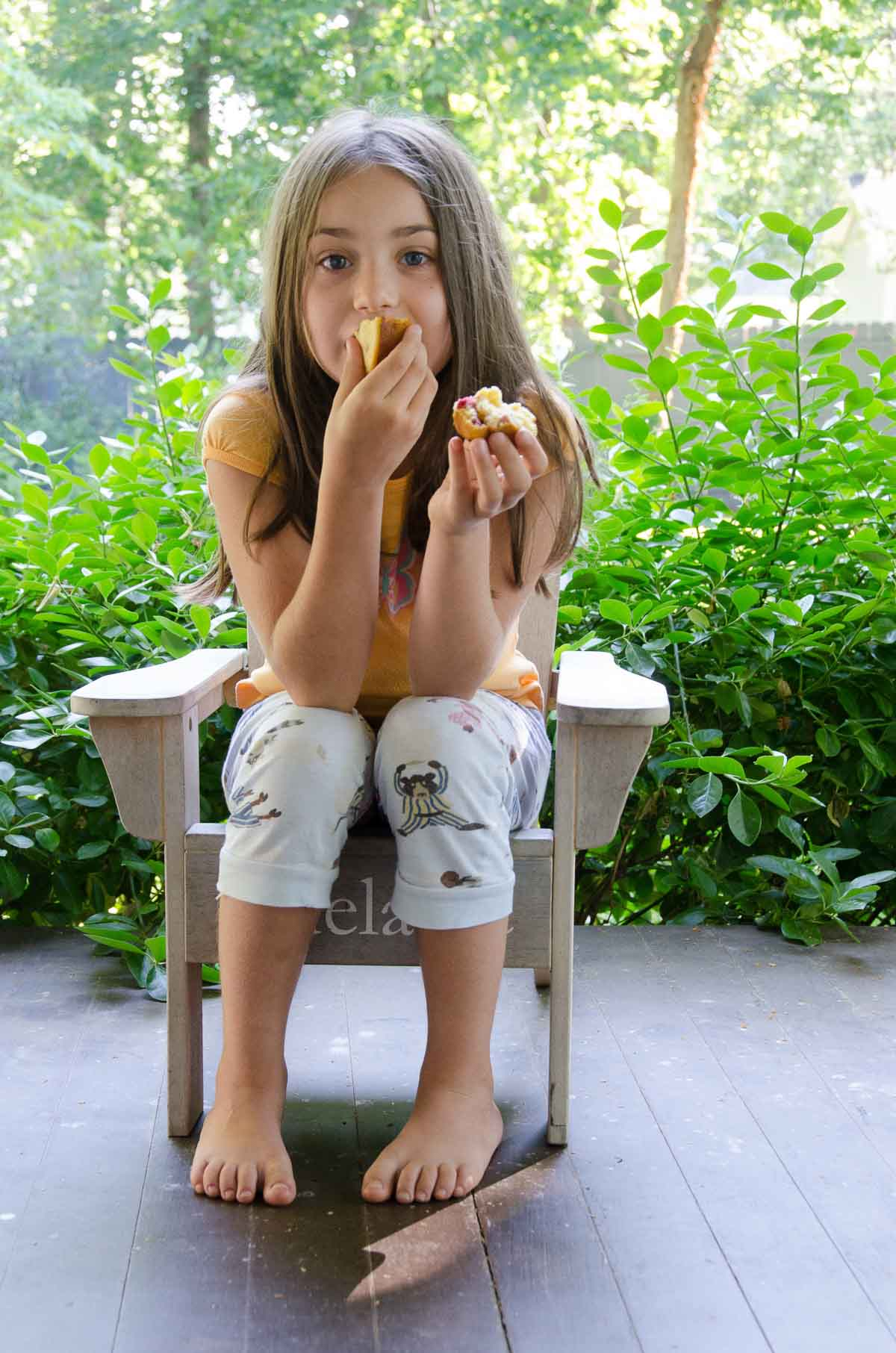 child eating a sour cherry muffin on the porch