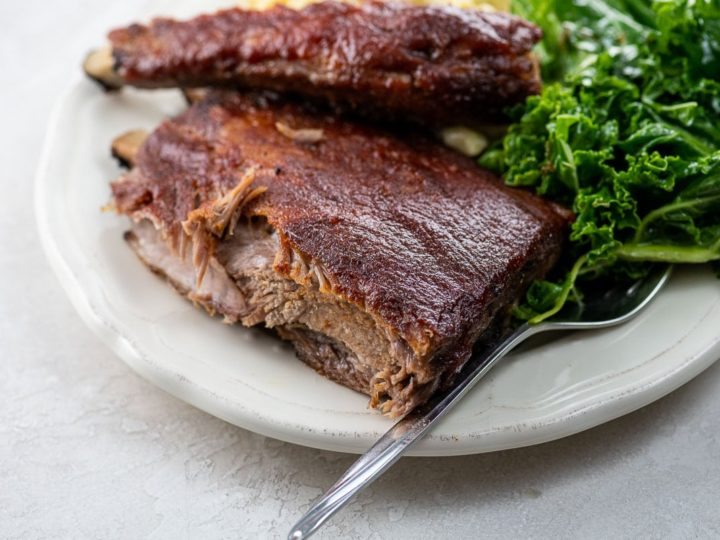 St. Louis ribs, kale salad, and macaroni and cheese on a plate