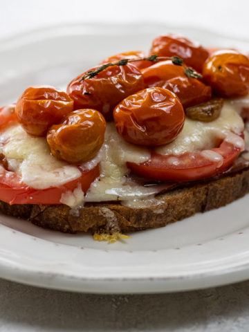 open face grilled cheese with ham, tomatoes, gruyere, and tomato confit on a plate