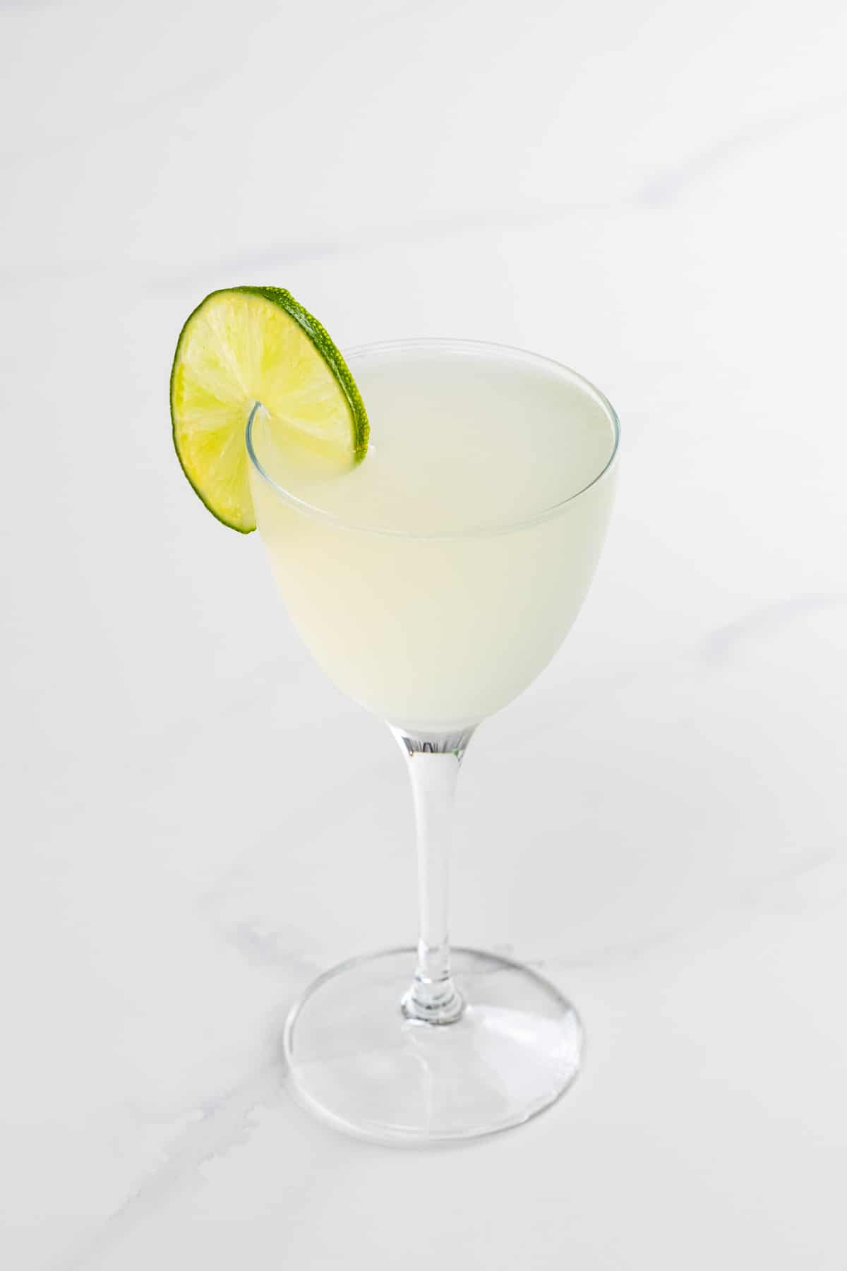 classic daiquiri in a nick and nora glass with a lime wheel garnish