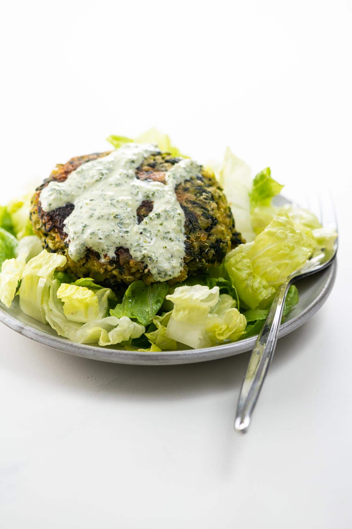 a fava bean burger on a small plate with lettuce and green goddess dressing