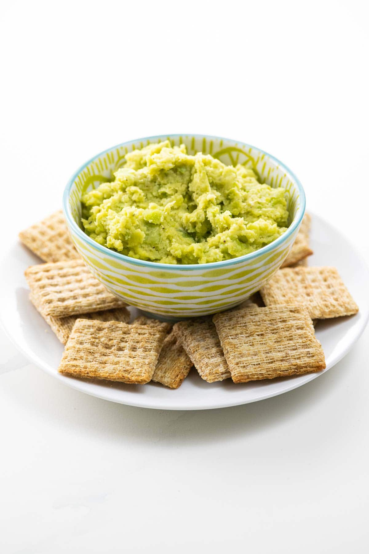 a bowl of fava bean puree with crackers on a plate