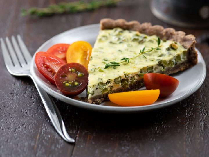 garlic scape tart with teff crust on a plate with tomatoes and a coffee cup