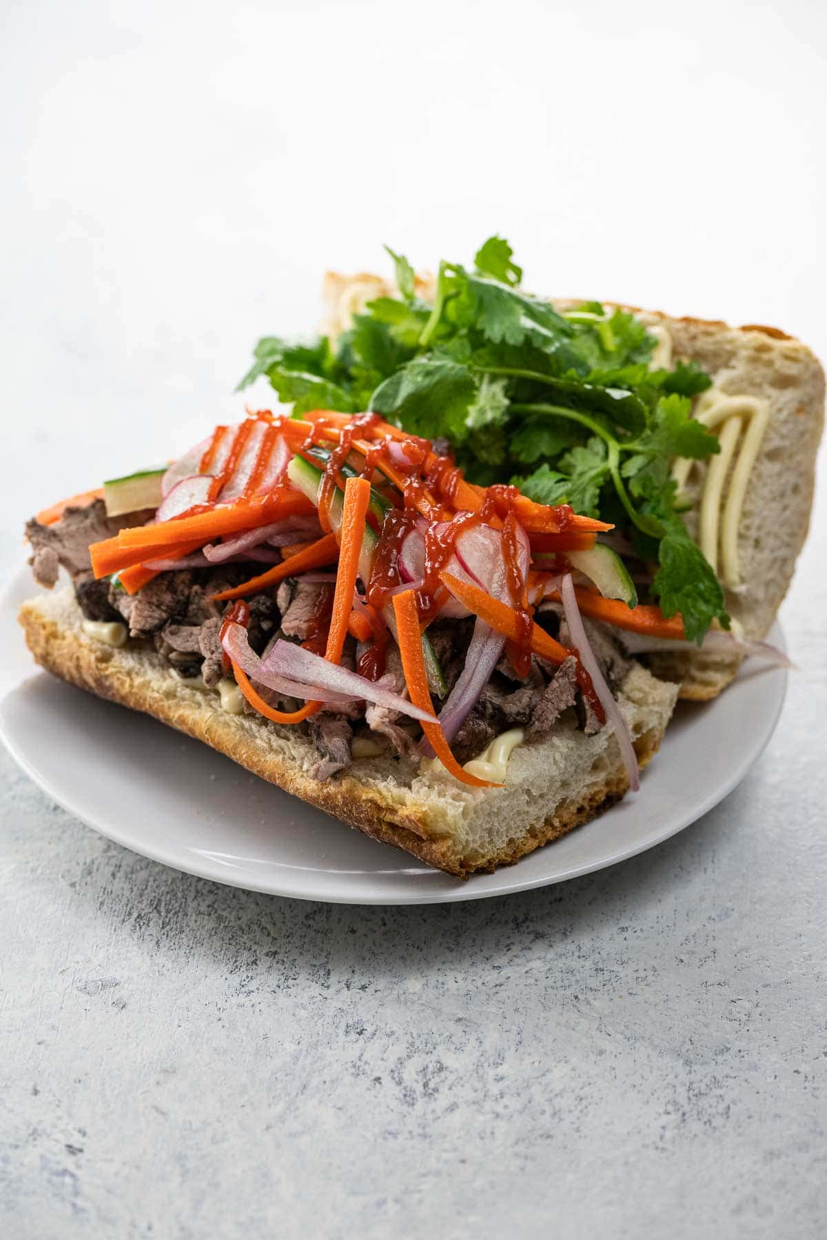 pork banh mi sandwich with pickled vegetables and cilantro on a white plate