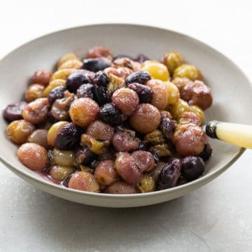 roasted grapes in a bowl with a spoon