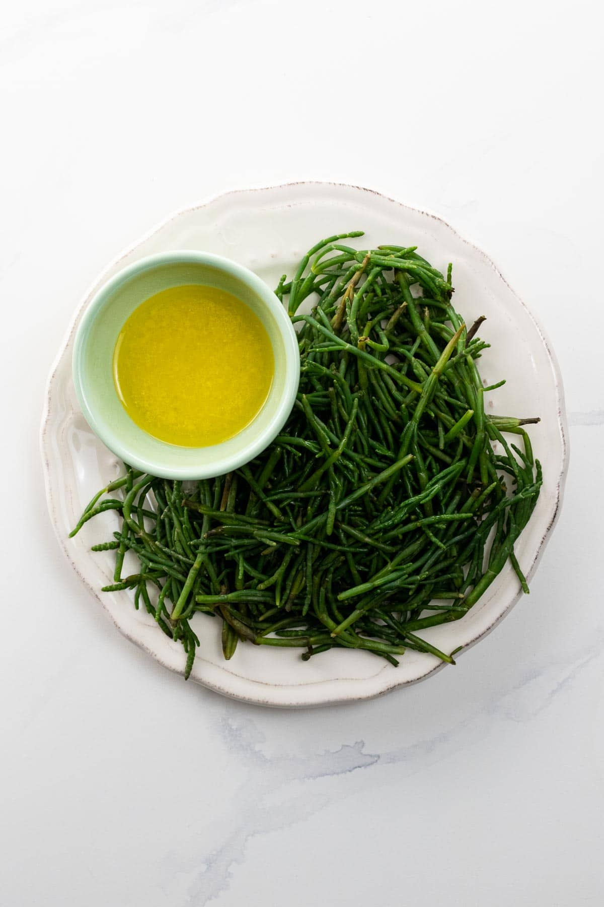 sea beans on a plate with a bowl of lemon butter for dipping