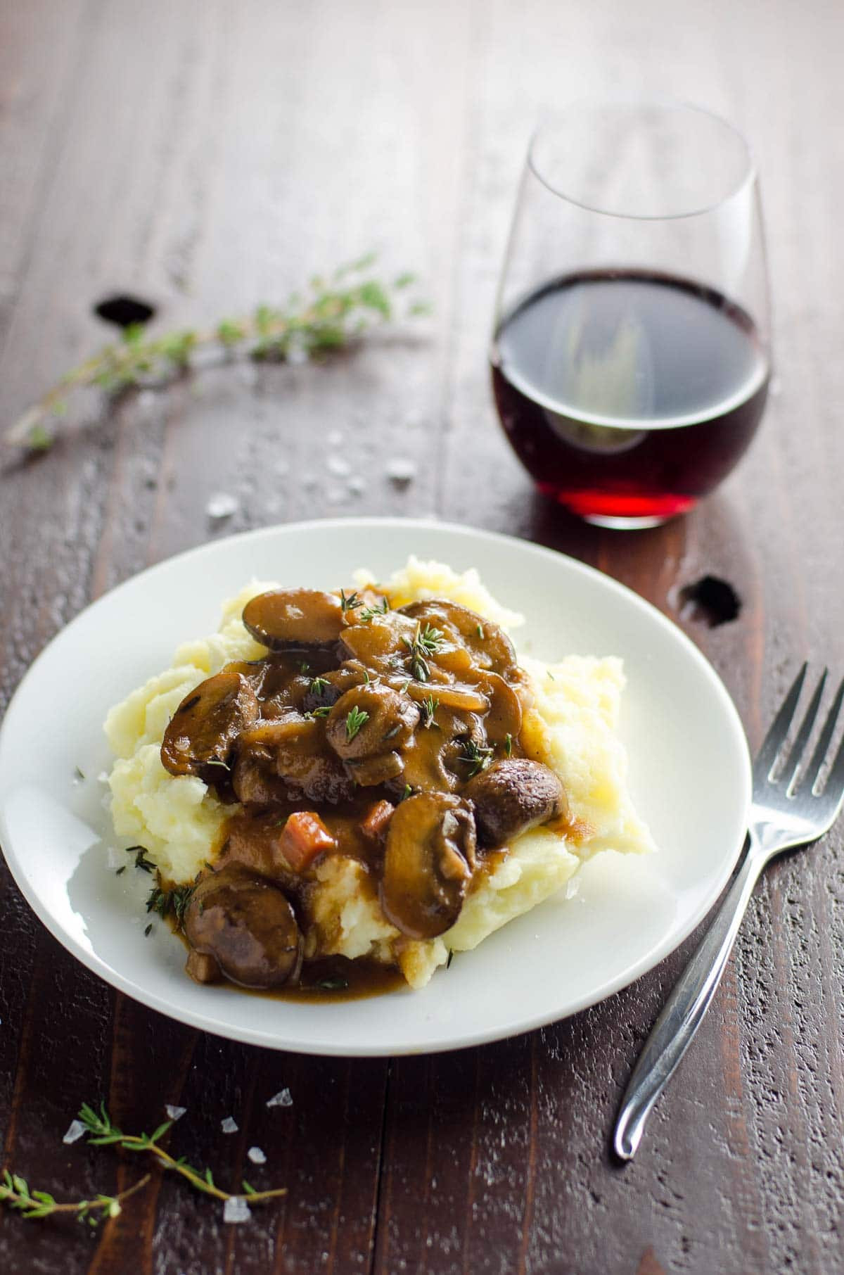 mushroom bourguignon (vegan option) on a plate with mashed potatoes and a glass of red wine