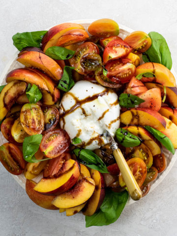 burrata caprese salad with nectarines on a serving plate