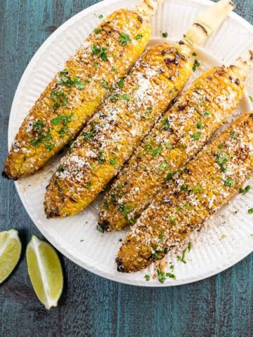 four elotes on a plate with lime wedges