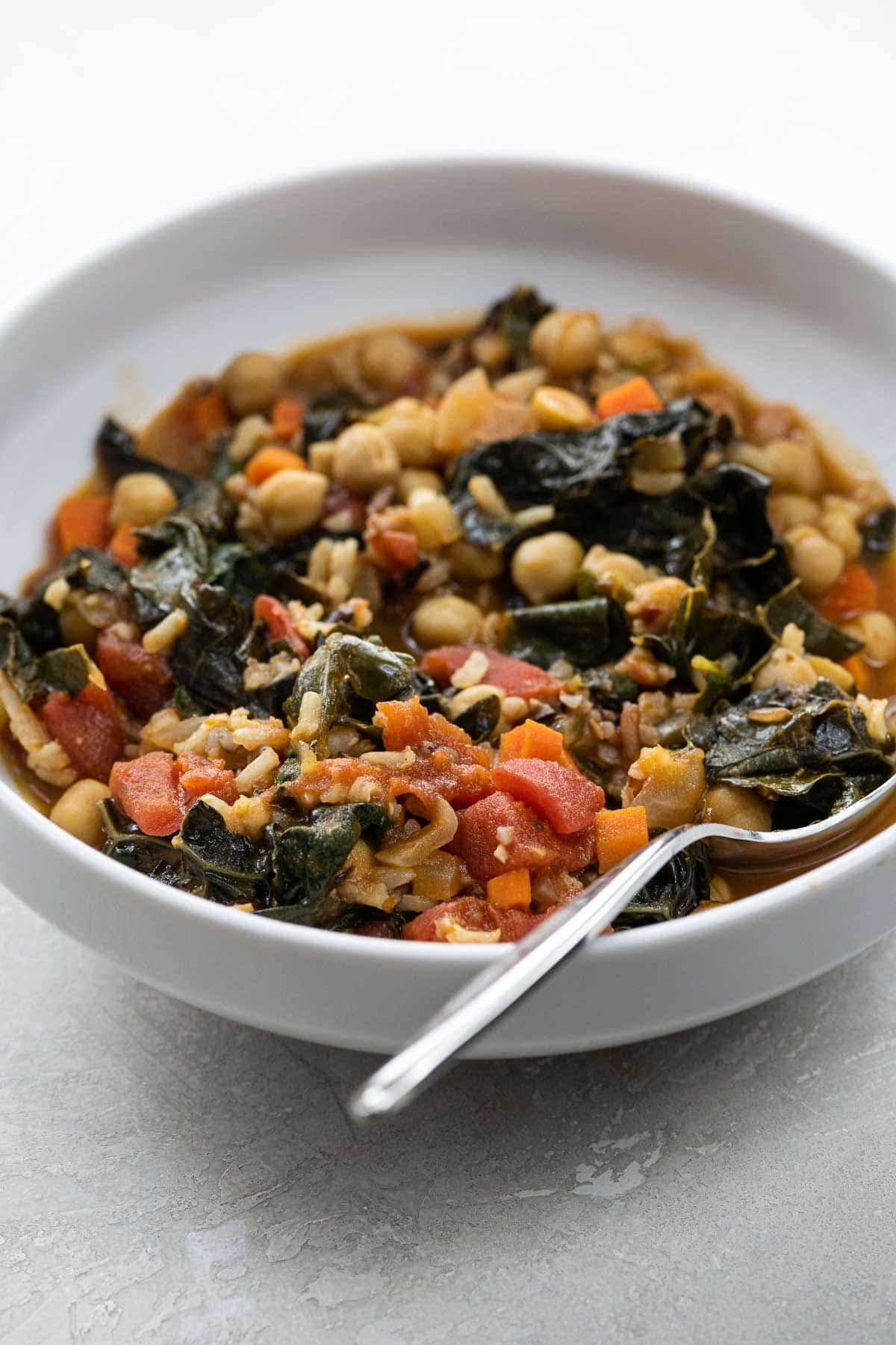 kale and chickpea stew in a white bowl with a spoon