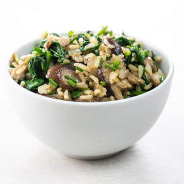 spinach mushroom rice in a white bowl