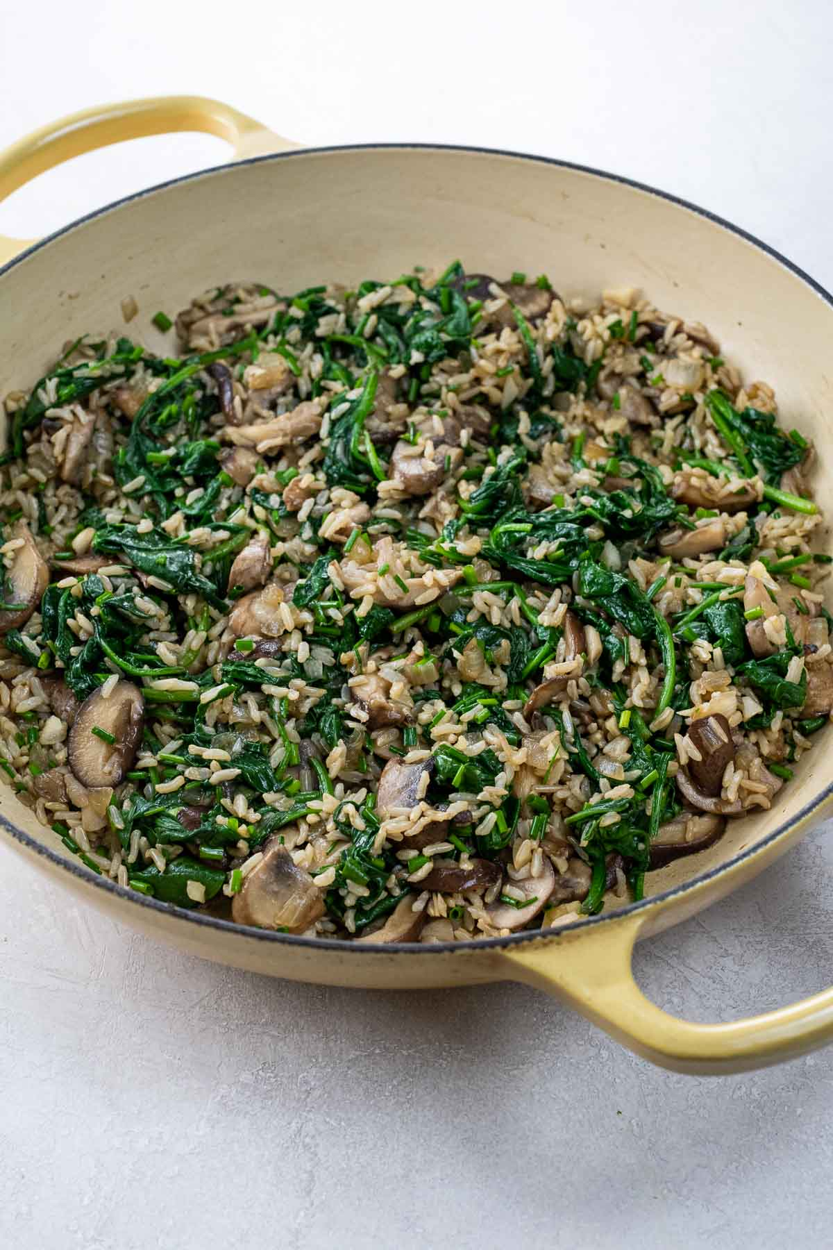 mushrooms and rice with spinach in a pan