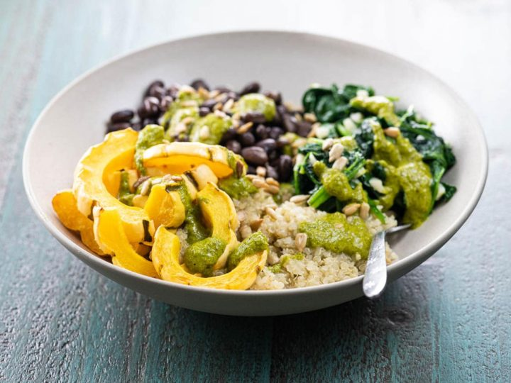 a quinoa power bowl with winter squash, spinach, and black beans