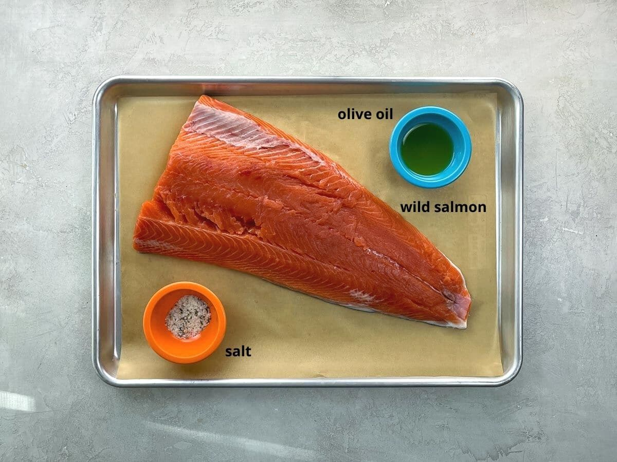 a raw wild salmon fillet, olive oil, and salt on a parchment lined baking sheet