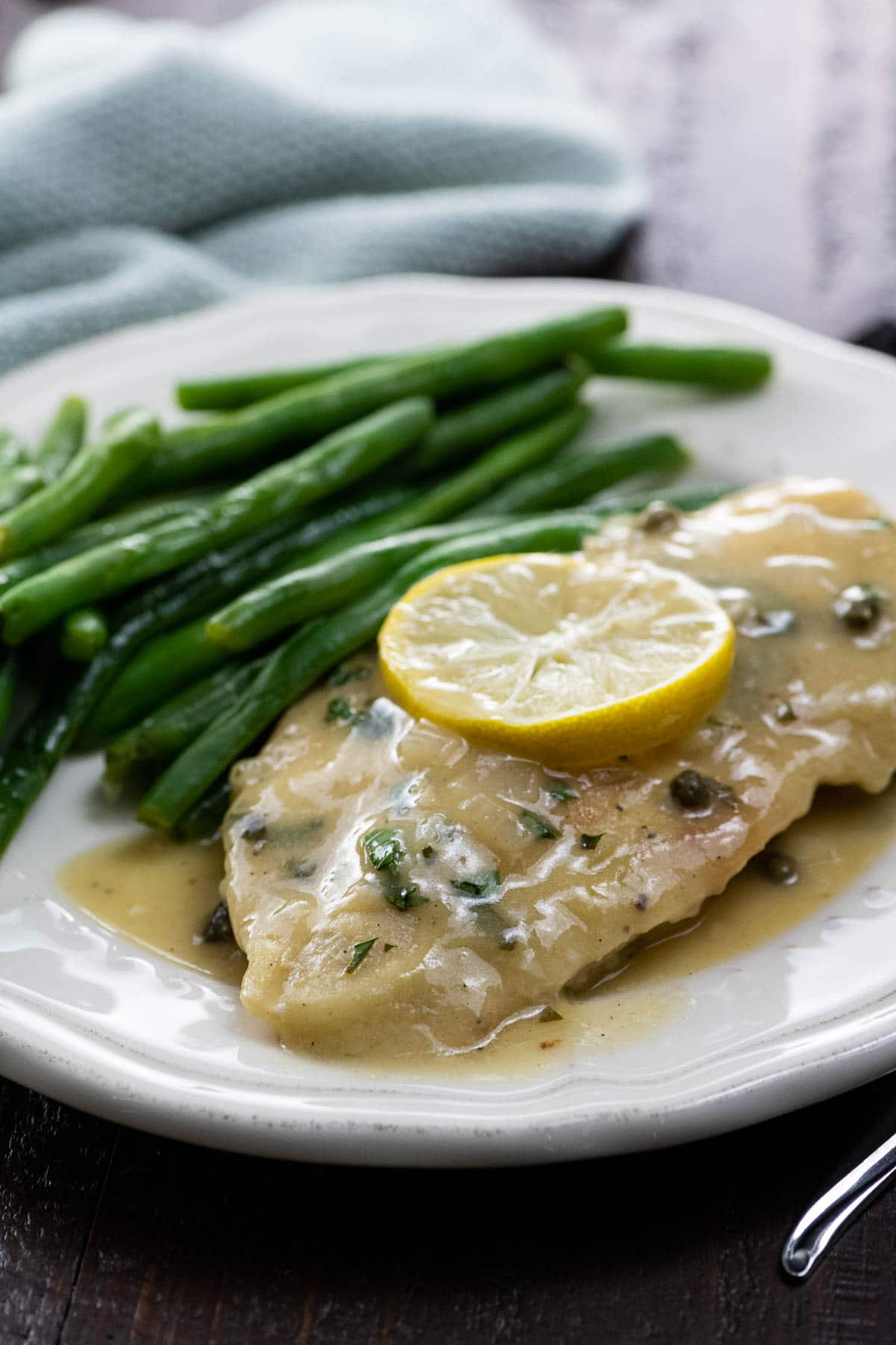 extra saucy chicken piccata on a plate with green beans and a lemon slice
