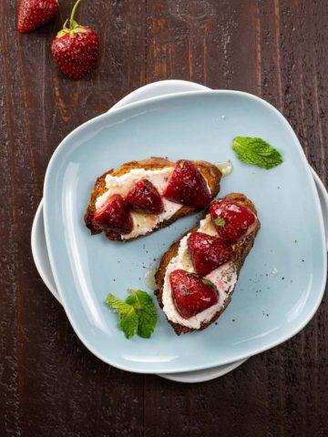 strawberry goat cheese bruschetta on a blue plate