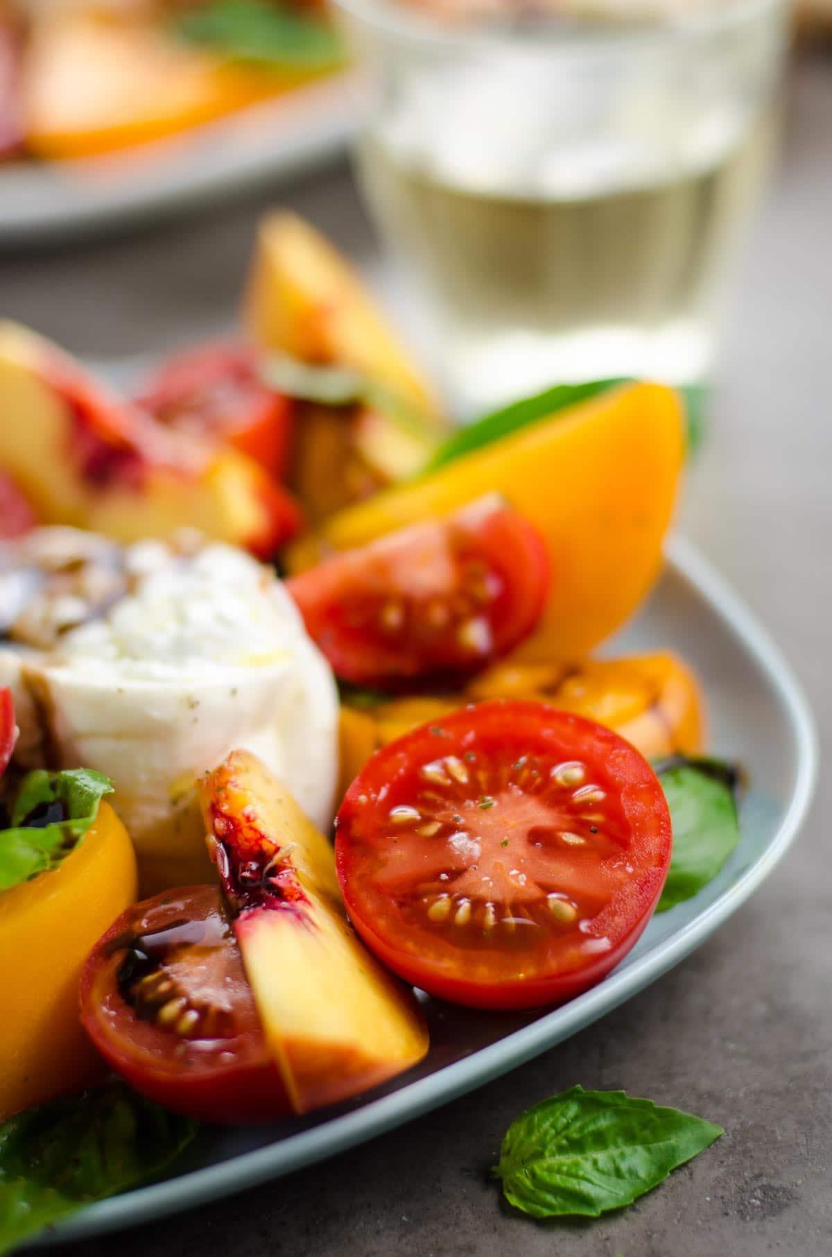 tomato nectarine burrata salad on plates with a glass of white wine