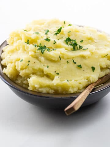 wasabi mashed potatoes in a bowl with a wooden spoon
