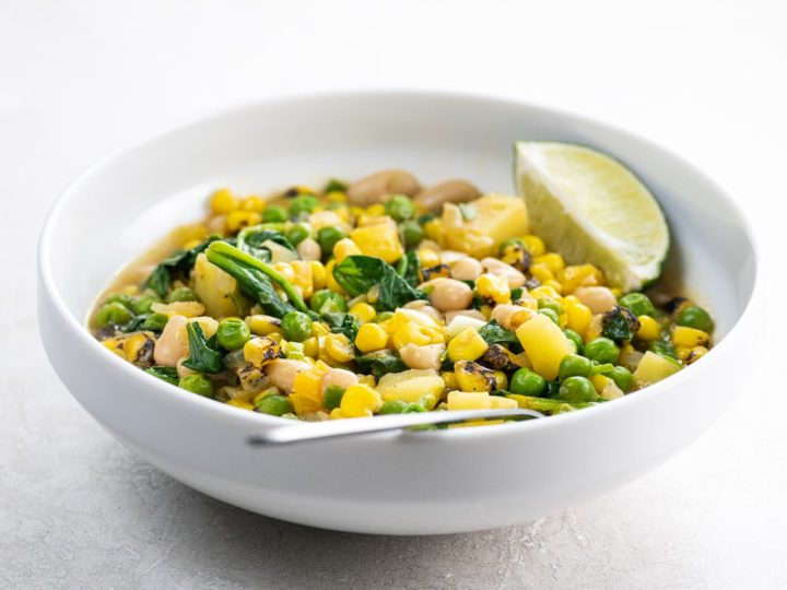 white bean stew with potatoes and corn in a white bowl with a spoon