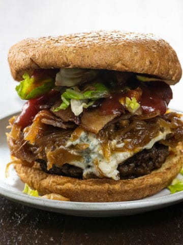 bacon weave blue cheese burger with caramelized onions, lettuce, and ketchup on a small plate