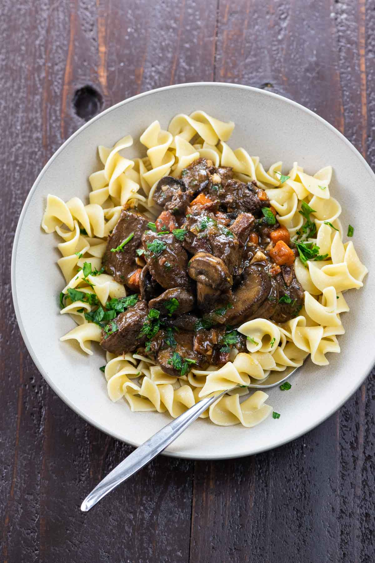 bouef bourguignon over egg noodles in a bowl with a fork