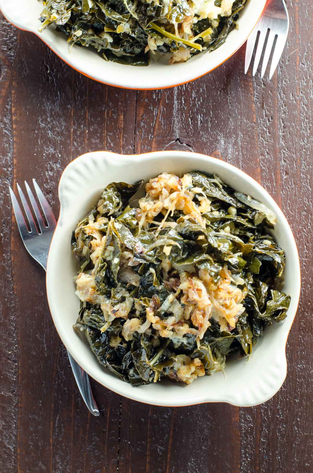 braised kale with caramelized onions, walnuts, and blue cheese in a gratin dish with a fork