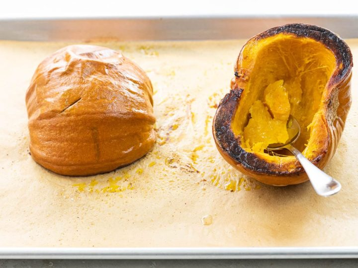 roasted pumpkin on a baking sheet with a spoon