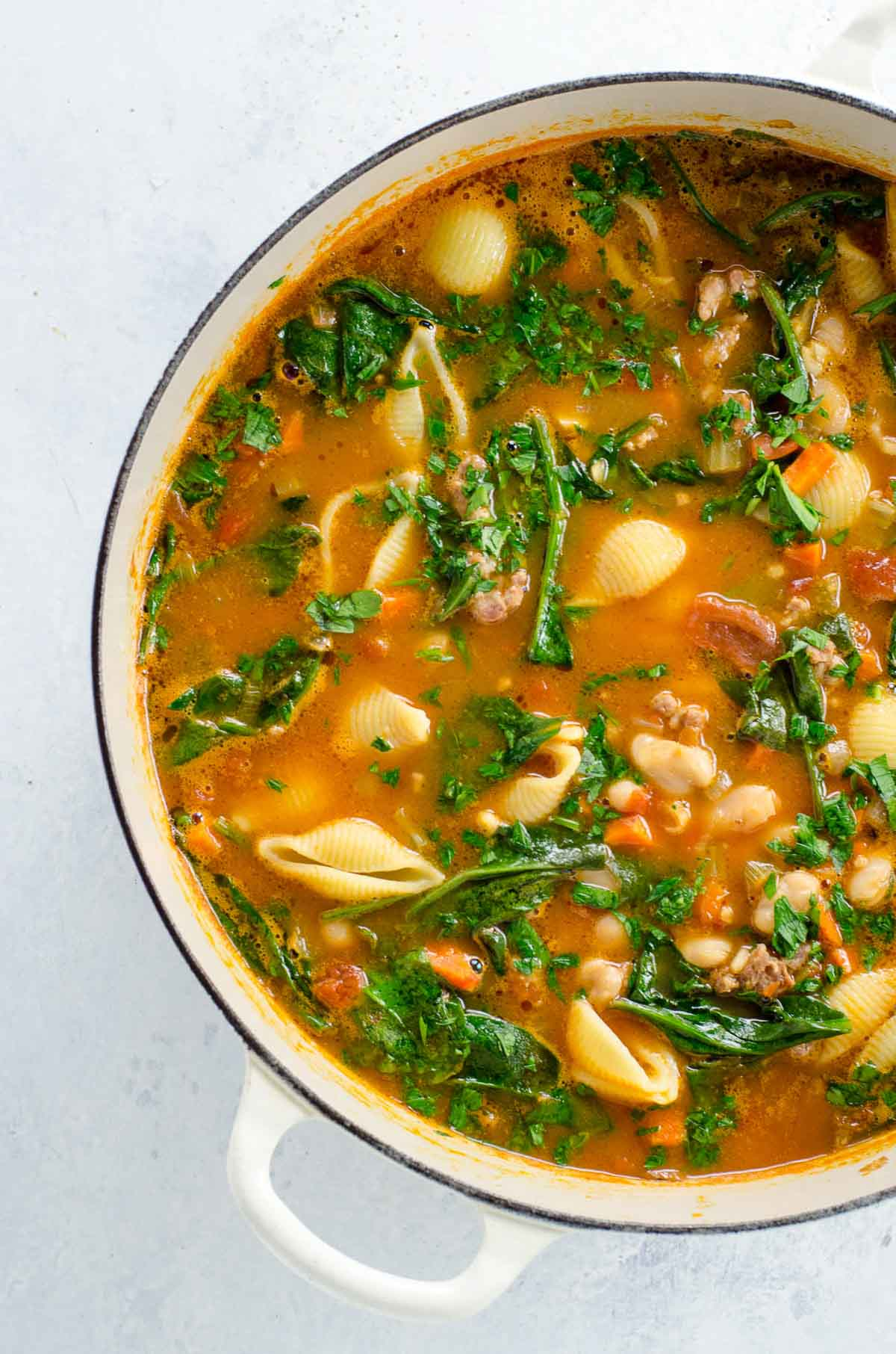 Italian sausage soup with white beans and spinach in a pot