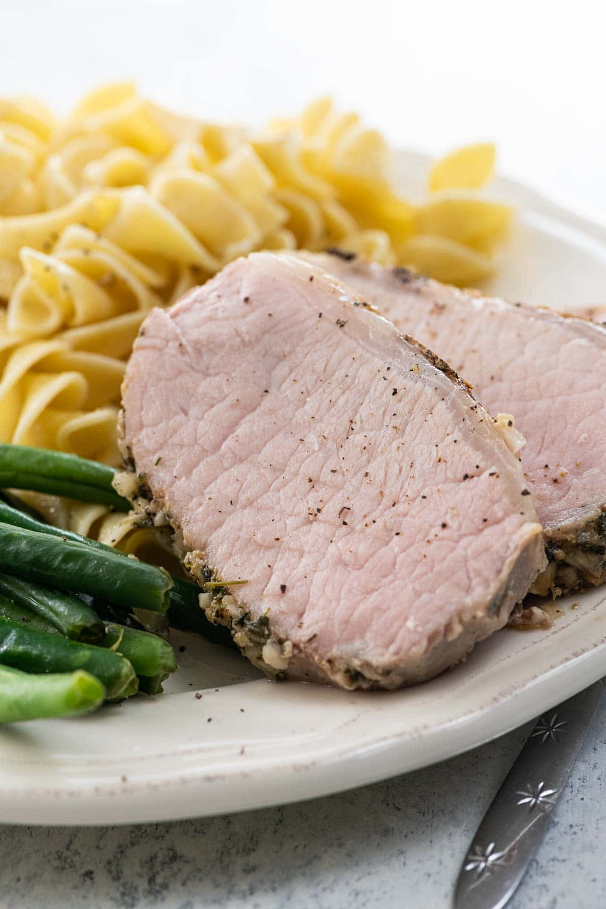 sous vide pork roast, green beans, and egg noodles on a plate