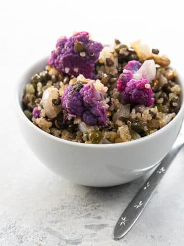 warm quinoa salad with lentils and cauliflower in a white bowl